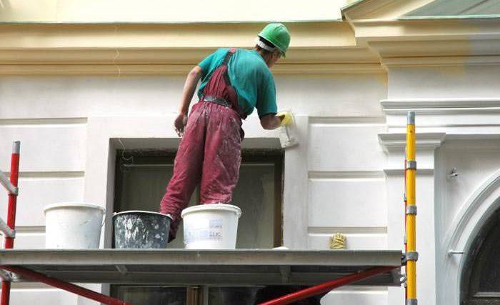 Albañil trabajando en una fachada subido a un andamio